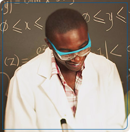 Man wearing goggles and a lab coat laughs in front of a blackboard