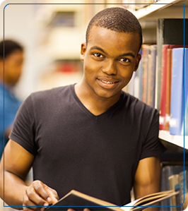 Smiling man holds book as he leans against a bookshelf in a library