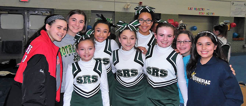 Cheerleaders and students pose together