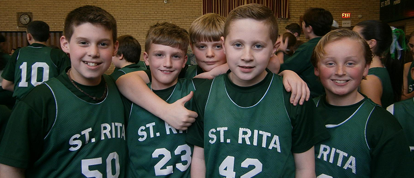 Five athletes wearing St. Rita jerseys pose together