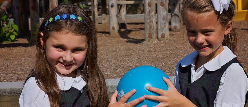 Two smiling students holding a ball outside in the playground