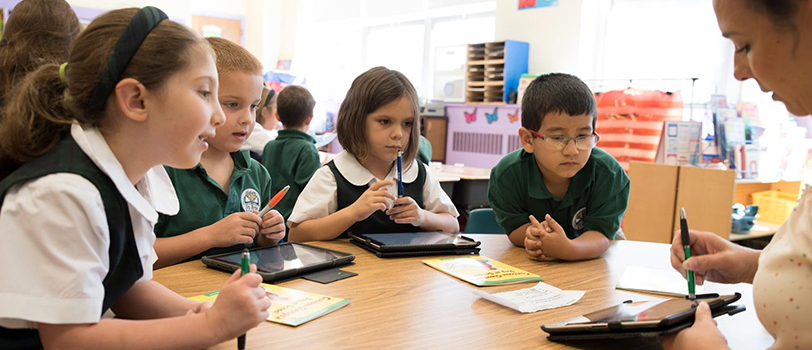 Students look at a teacher holding a tablet