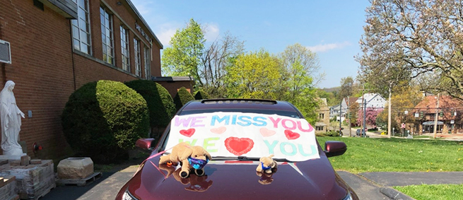 Car with WE MISS YOU poster on top