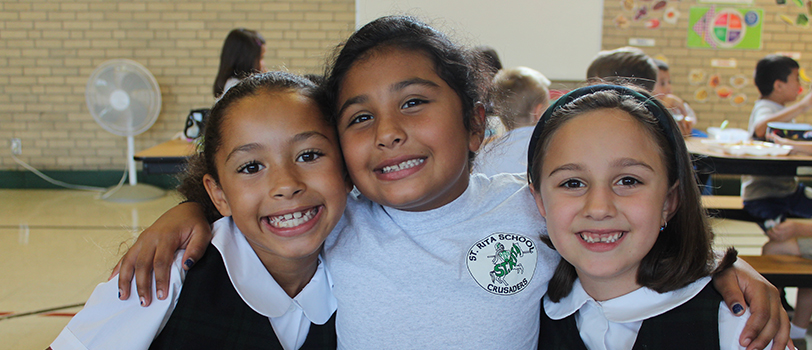 Three happy St. Rita school girls in their school uniforms