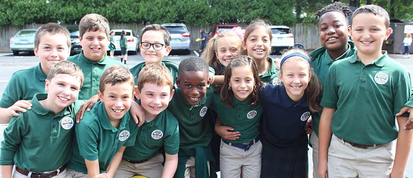 Group of St. Rita School students in green uniform polos posing for a picture outside