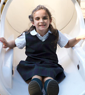 Young smiling female student slides down the slide