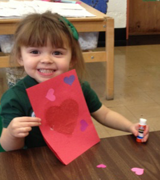 Young smiling student holds up a Valentine's Day craft
