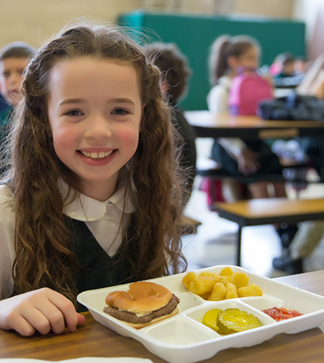 Smiling student sits with her lunch on the table