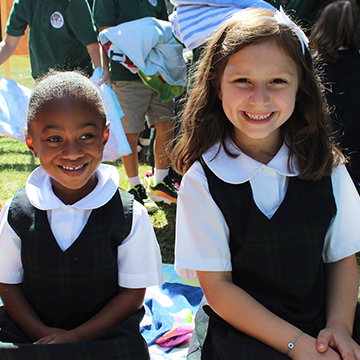Two smiling students enjoying an outside activity