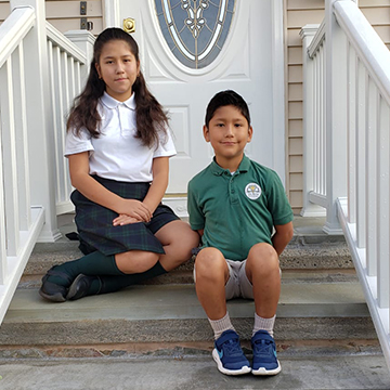 Two St. Rita siblings posing for a picture at home