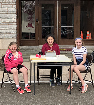 3 students outside at a table