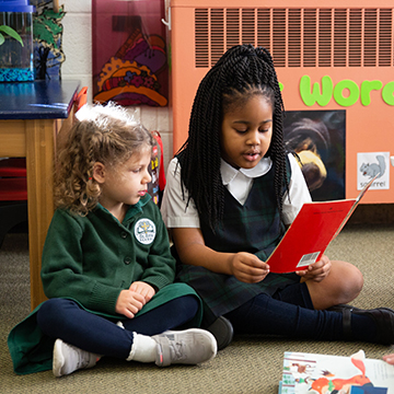 Two young students reading together