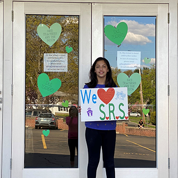 Middle school student holding up We love SRS sign