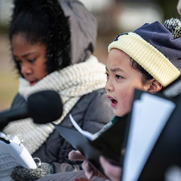 Young girls bundled up and singing outside