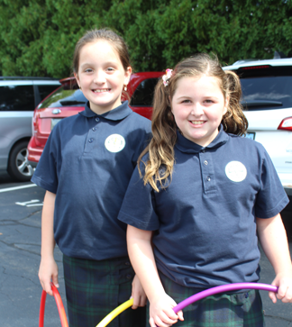 Two girl students holding hula hoops