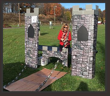 Staff member stands behind a cardboard castle