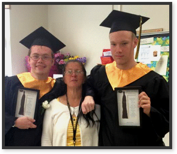 Graduates hold diplomas as they pose with a teacher