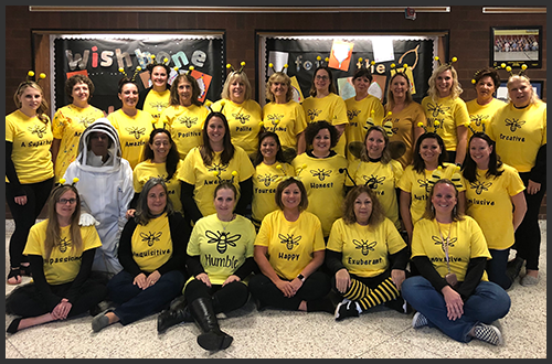 Staff members wearing bee headbands and bee t-shirts pose together