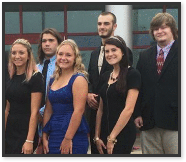 Students dressed in fancy attire pose outside