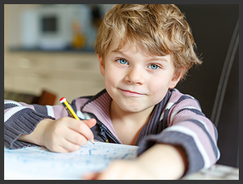young boy with paper and pencil