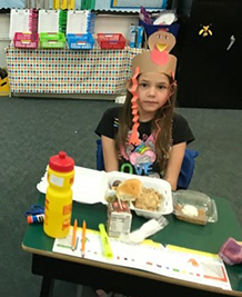 Female Student wearing turkey hat eating thanksgiving meal