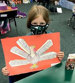 Female student holding turkey art project