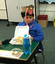 Male student wearing turkey hat and eating thanksgiving meal