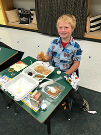 Male student eating thanksgiving meal at desk
