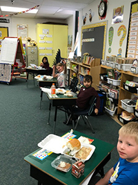 Group photo of students eating thanksgiving meal at desks