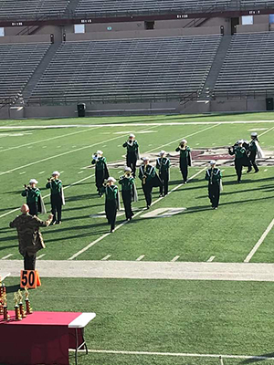 Cloudcroft band on the football field led by director