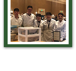 Group of students in culinary attire posing with an award together
