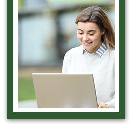 Young lady smiling while working on her laptop outside