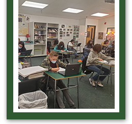 students writing at their desks in the classroom