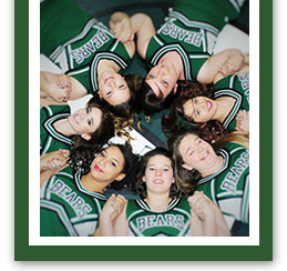 Cheerleaders holding hands pose together as their heads form a circle