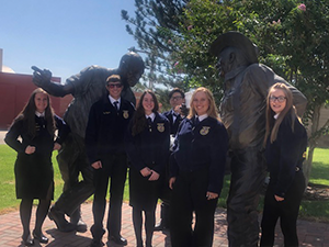FFA members pose with statues outside