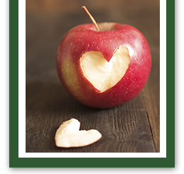 Red apple with a heart-shaped bite taken out of it