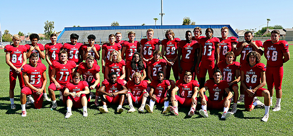 Football team members pose together on the football field