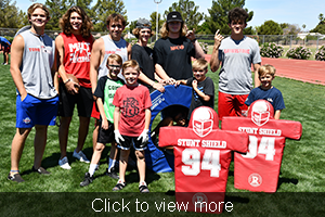 Click to view more. Campers and seniors pose outside with a stunt shield.