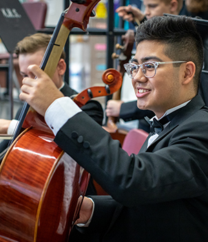Happy male student playing a stringed instrument