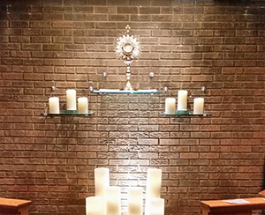 Candles and prayer materials forming a cross shape