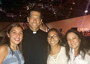 Three happy StAY youth members posing for photo with Father Mike