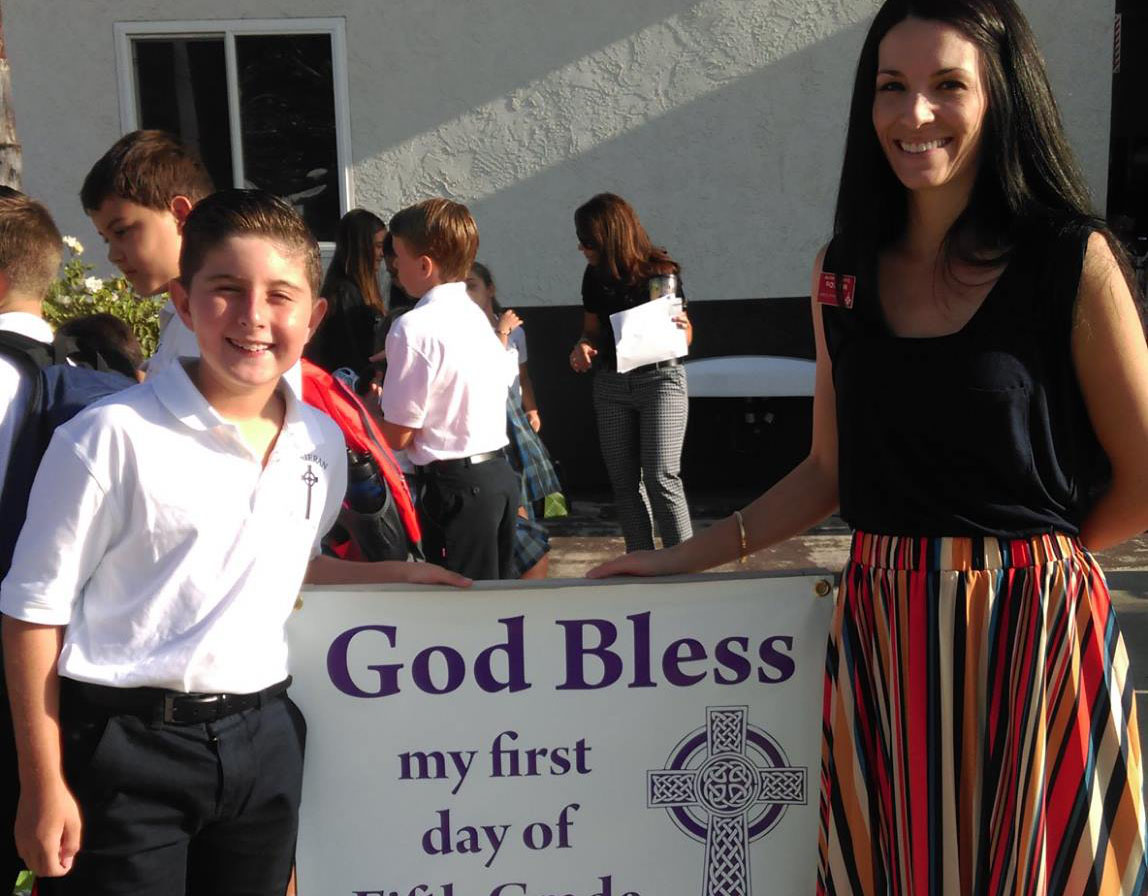 Student and adult pose next to a sign reading God Bless My First Day of Fifth Grade