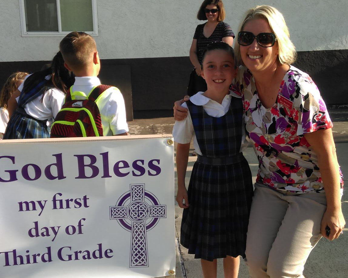 Adult and student stand next to a sign reading God Bless My First Day of Third Grade