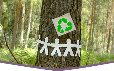 A tree in the forest with a recycling logo and paper craft people attached to it
