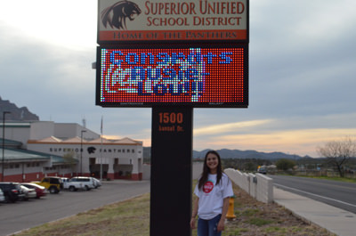 Augustine Hing standing next to SUSD sign that reads, Congrats Augie-Lou!!!