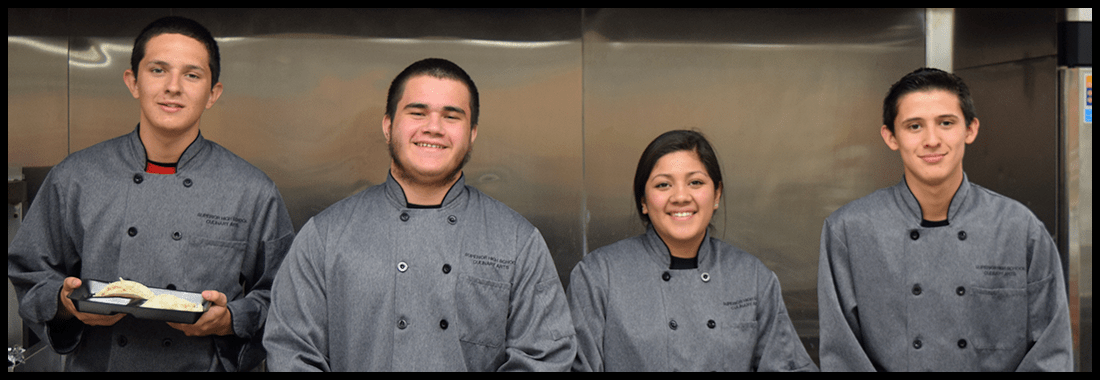 Students in chef uniforms pose together in a kitchen