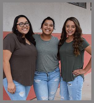 Three female students pose outside