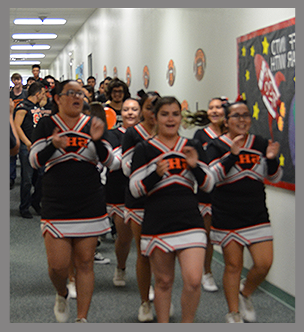 Cheerleaders cheer in a hallway