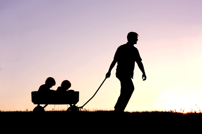photo of silhouette of father pulling a wagon
