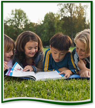 Four students read from a book in grass